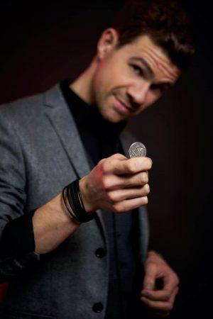 Zauberkünstler Dominik Fontes für private Feiern mit Münze in der Hand auf einem Geburtstag